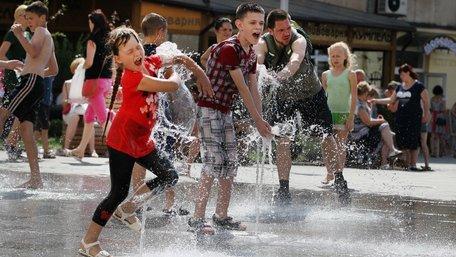 Десятки дітей рятуються від спеки у сухому фонтані у центрі Львова. Фото дня