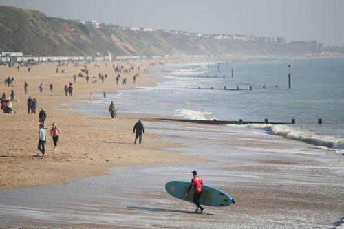Люди відпочиваютт на пляжі у місті Бонрмут на узбережжі проливу Ла-Манш у Великій Британії