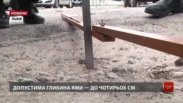 У Львові патрульні поліцейські лінійкою вимірюють глибину ям на дорогах