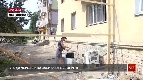 Мешканці через вікна виносять свої речі із другого під'їзду обваленого будинку у Дрогобичі