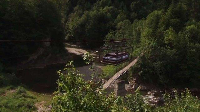 Труни з небіжчиками у гуцульському селі переправляють до церкви канатною дорогою. Фото дня